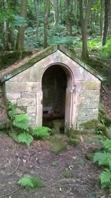 stone structure with antique water pump inside (over a natural spring)
